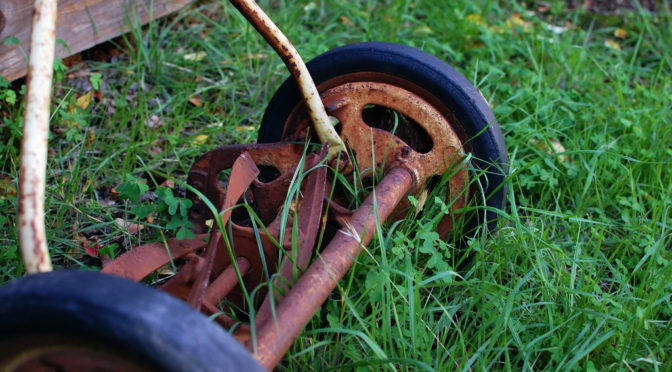 An old lawn mower in grass